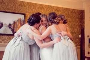 Bride and bridesmaids cuddling before ceremony