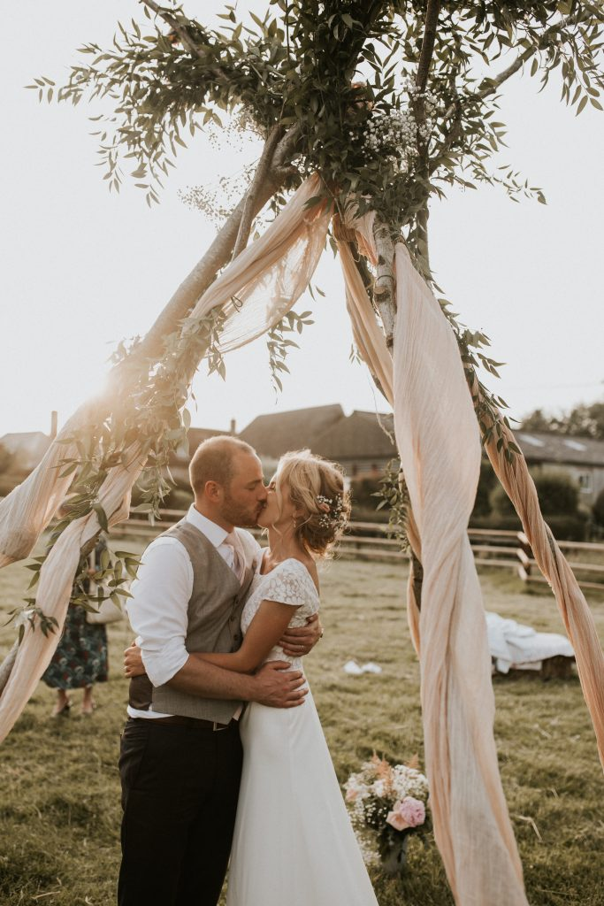 Bride styled by Bridal Hair in Hampshire kissing groom under rustic archway