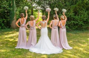 Bride and bridesmaids styled by Bridal Hair in Hampshire with bouquets in the air